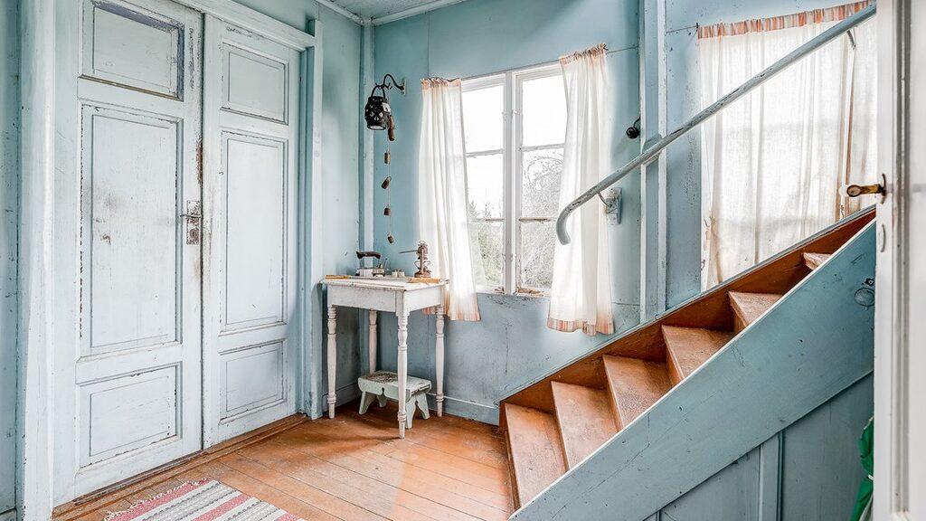 Entré med dubbeldörrar. Hallen har trägolv och målade väggar samt trappa till övervåningen.