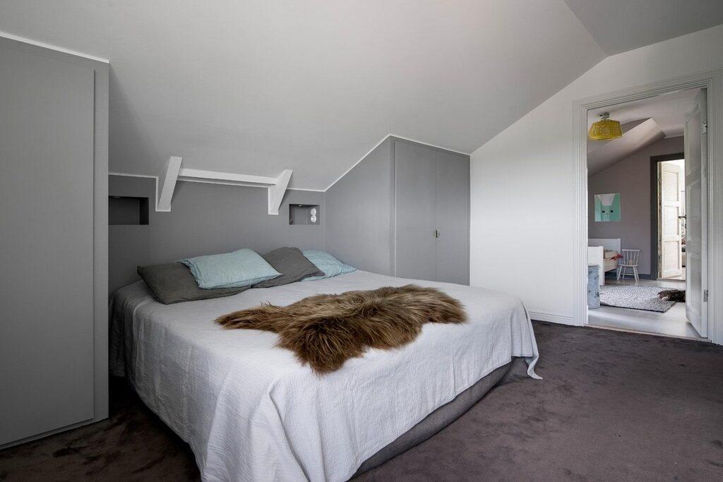 Master bedroom, ett hörnrum med sjöutsikt via stort, halvmåneformat fönster. Gott om plats för såväl dubbelsäng som annan möblering. Heltäckningsmatta, vita och gråa väggar. Bra förvaring i kattvinden samt nybyggd belysning ovanför sängen.