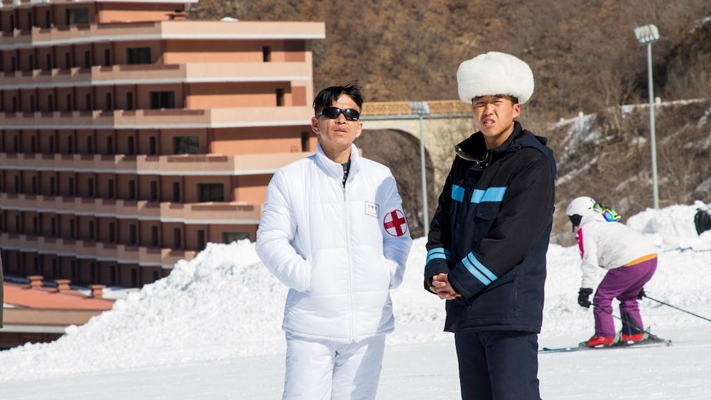 Backläkaren i Masikryong betraktar skidåkarna. Gröna och blå backar dominerar.