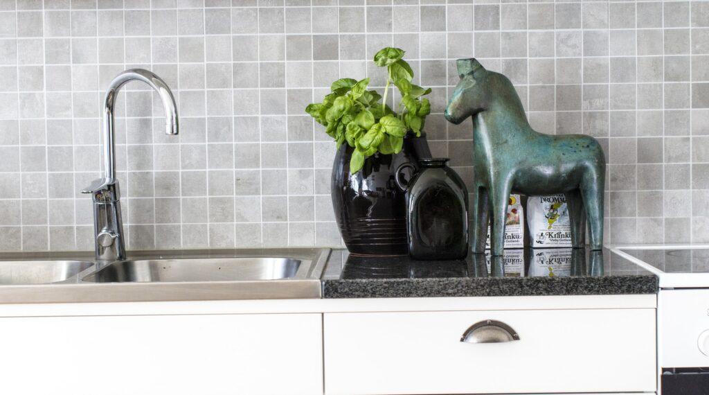 Det nyrenoverade köket har  rostfria detaljer mot en fond av grå mosaik. Hästen är en skulptur i brons av Andreas Wargenbrant.