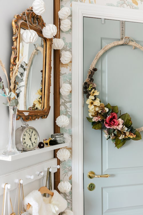 Den vackra dörrkransen är tillverkad av en gammal ring från en sänghimmel, som i sin tur virkats med hampasnöre och dekorerats med plastblommor. Garderobsdörren har Mia målat i en vacker gråblå nyans.
