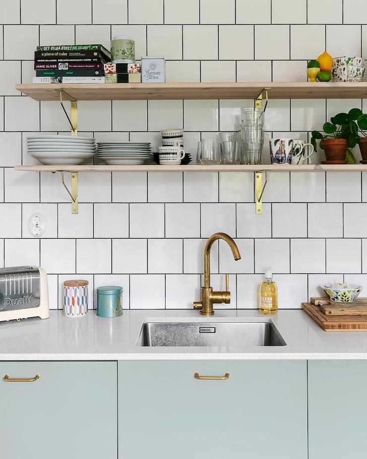 Köket renoverades 2018 och fick gröngrå inredning från Ikea och bänkskivor av komposit. Köket är rymligt och känns ännu luftigare tack vare de öppna hyllorna, från Marbodal, som valts i stället för traditionella överskåp.