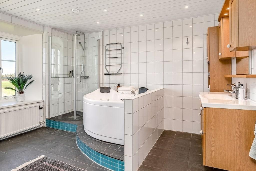 Badrummet på övre plan är rymligt med både badkar och dusch. Badkaret är uppbyggt med utsikt ut mot de öppna fälten mot väster. Duschen är placerad i ena hörnet, även den är uppbyggd likt badkaret och har vikbara duschväggar.