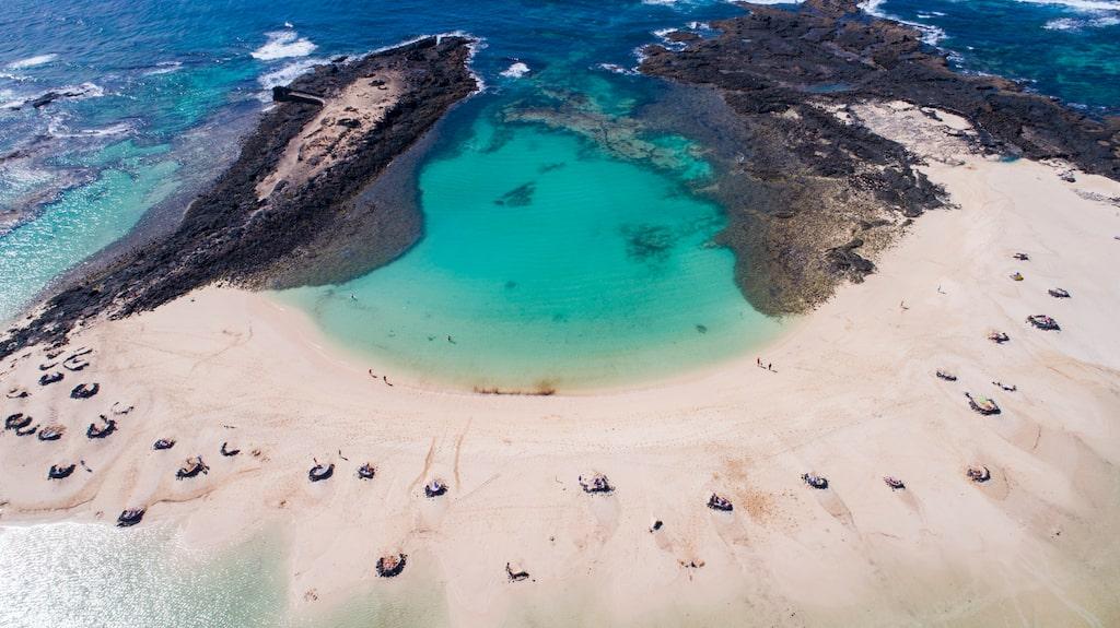 På La Conchas strand finns vindskydd i form av svart lavasten.
