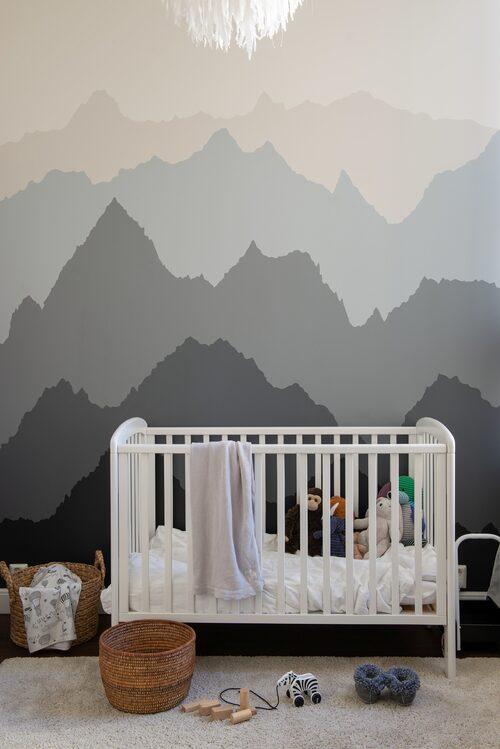 I Dions rum har Elin målat formerna av berg med en liten sminkpensel.