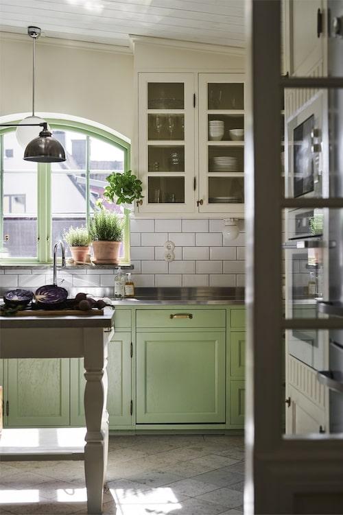 En glimt in i det fina köket. Färgen går i stilren grön nyans med knoppar i guld och träpanel på väggarna.
