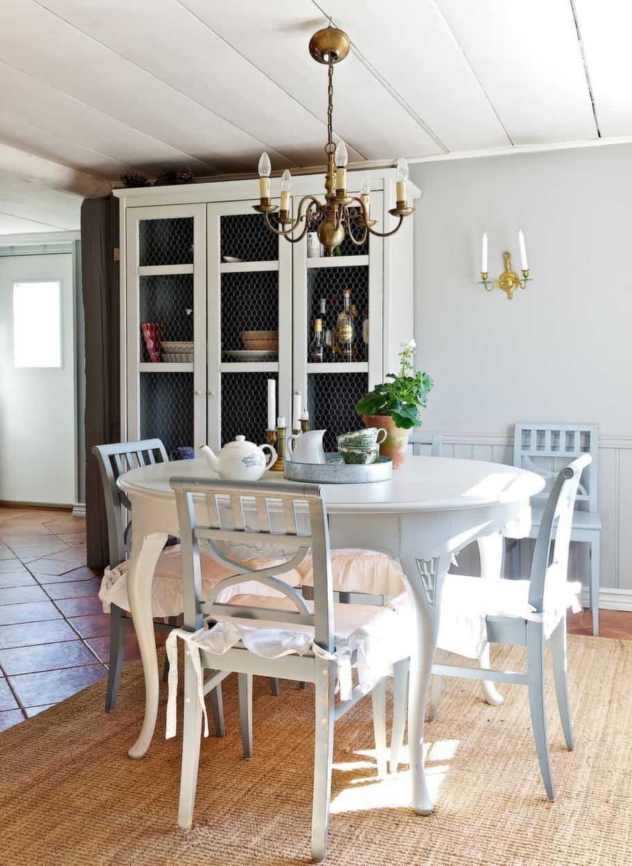 MATPLATS<br>I köket står en matgrupp med fyra ljusblåa Östgötastolar. Den sortens stolar har tillverkats i Östergötland av olika bysnickare sedan 1800-talet. Skåpet från Ikea har Catarina målat och satt i hönsnät i.