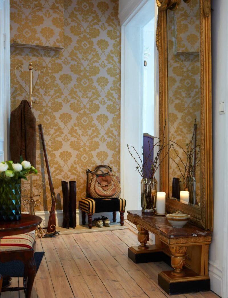 Maffig hallspegel med hallbord i röd marmor och snidade ben. Guldmönstrad medaljongtapet med lila botten, Designers guild.