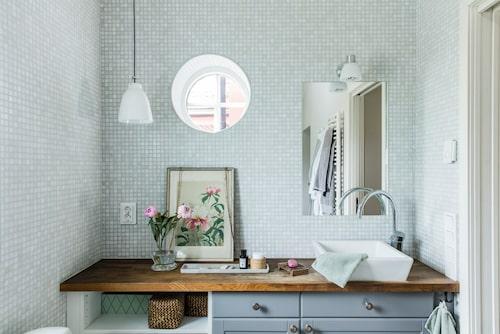 Det stora badrummet är klätt med glasmosaik och har skåp från Ikea. Taklampan är en Caravaggio från Lightyears. Den rara tavlan är köpt i loppisbutiken Lata Pigan utanför Enköping.