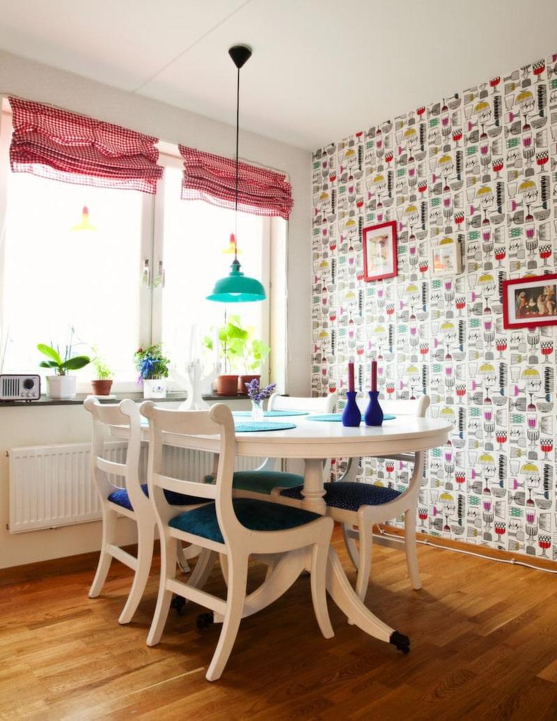 Färgstark fondvägg. Köksmöblerna har familjen ärvt av Stefans föräldrar. Bordet och stolarna var från början i mahognyfärgat trä, Sara målade allt vitt och fixade nya fina tyger till stolsitsarna.
