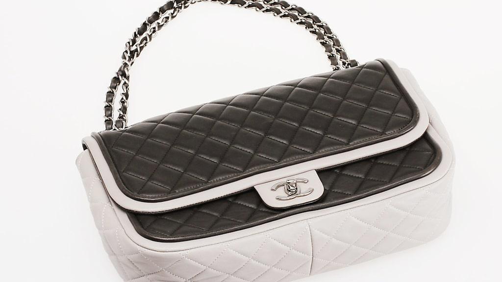 Väska, Chanel. Quiltat tvåfärgat läder, detaljer i vitmetall. Längd 30 cm, höjd 20 cm, djup 8 cm. Slutpris: 13 500 kronor.