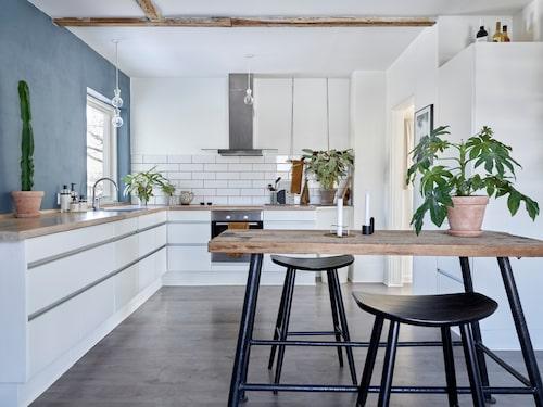 Den gråblå väggen ger köket värme och karaktär. Här umgås paret med vänner och arbetar vid matbordet. Köksinredningen från HTH är begagnad och köpt på Danmarks motsvarighet till Blocket. Köksbordet kommer från en nedlagd gård. Stolarna kommer från Cult Furniture.