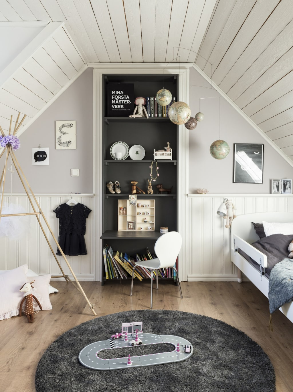 Roger har platsbyggt en bokhylla i Elvas rum där det tidigare var en dörr. Mobil med glober i taket från Artilleriet. Matta från Ikea. Stolen är ifrån Mio.