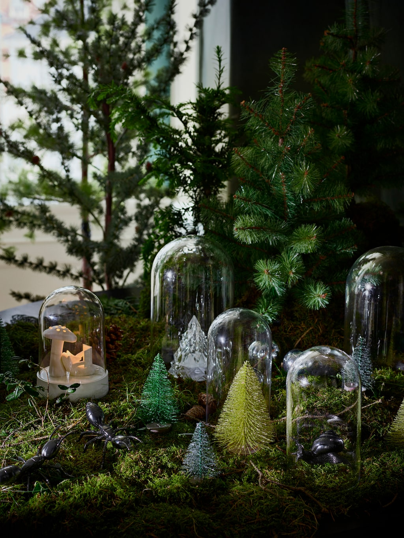 Bordsdekorationer med igelkott, myra, snigel och konstgjorda växter.