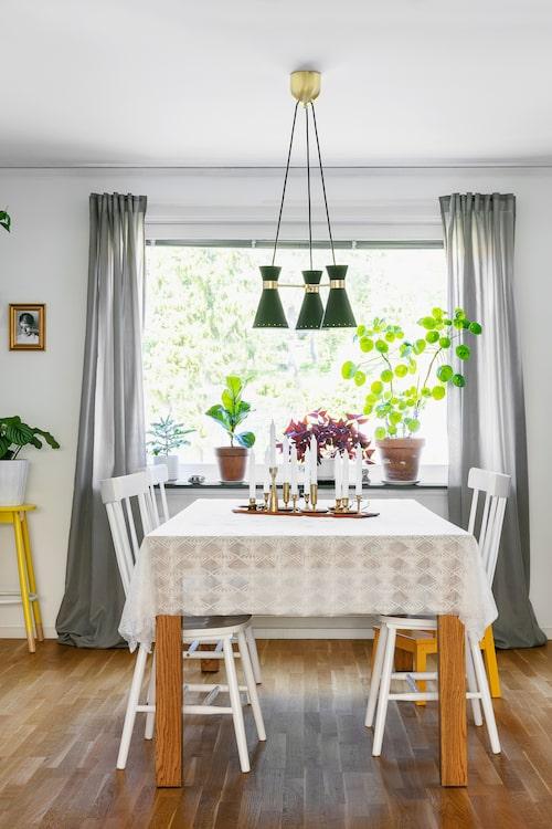 På det rymliga bordet i matsalsdelen står en stor samling mässingsljusstakar i olika modeller, både arvegods och loppisfynd. Matbord, Mio. Stolar, Furniturebox. Taklampan i retrostil, från Ikea.