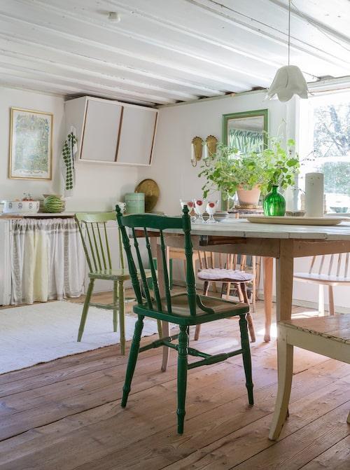 Under en plastmatta dolde sig trägolvet som ger gedigen karaktär. Stolar och bord är loppisfynd.