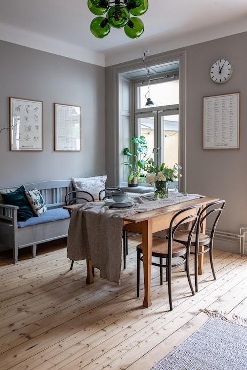 Matplatsen har ett träbord som är köpt via Instagram av @villabjorkhaga. Stolar, Thonet. Linneduk, Hemtex. Porslin från Rörstrand och Åhléns. Kökssoffan kommer från Katarinas föräldrars gård i Skåne. Pläd, H&M Home. Stor linnekudde, Ikea. Mönstrad kudde, H&M Home. Grön sammetskudde, Ikea. De inramade planscherna i köket, Kunskapstavlan. Grön taklampa, House Doctor. Matta, Tell me more.
