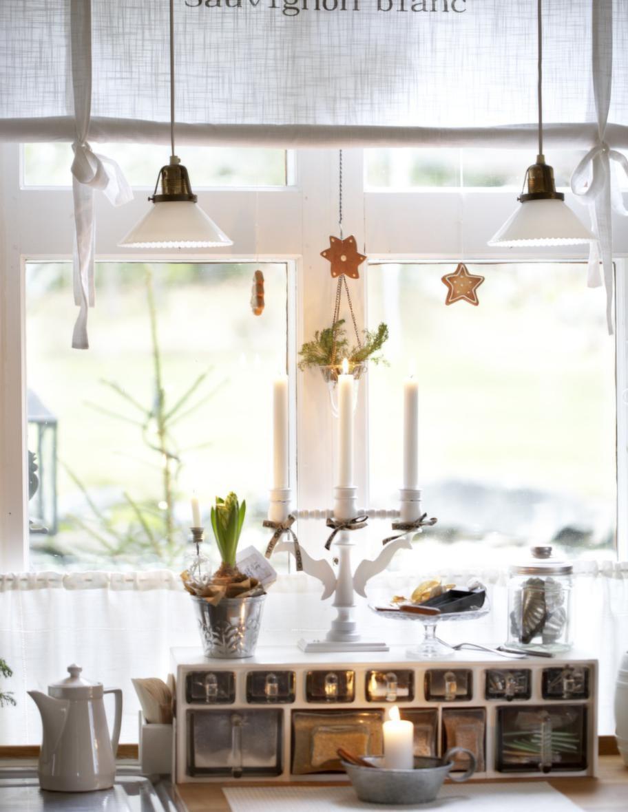I FÖNSTRET<br>Med pepparkakor på snöre och julblommor skapar Tarja jul. Den fina träljusstaken har hängt med i många år.