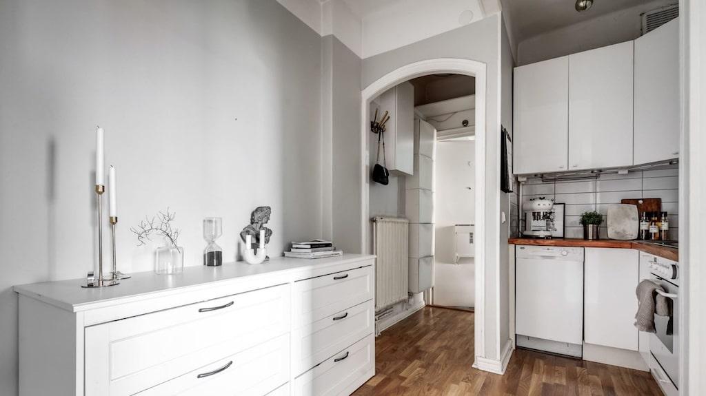 Hallen leder rakt in i köket med fiskbensparkett och gråmålade väggar med vita inslag. Säkerhetsdörren i hallen har kamera och elektroniskt lås som går att låsa upp med en app eller vanlig nyckel.