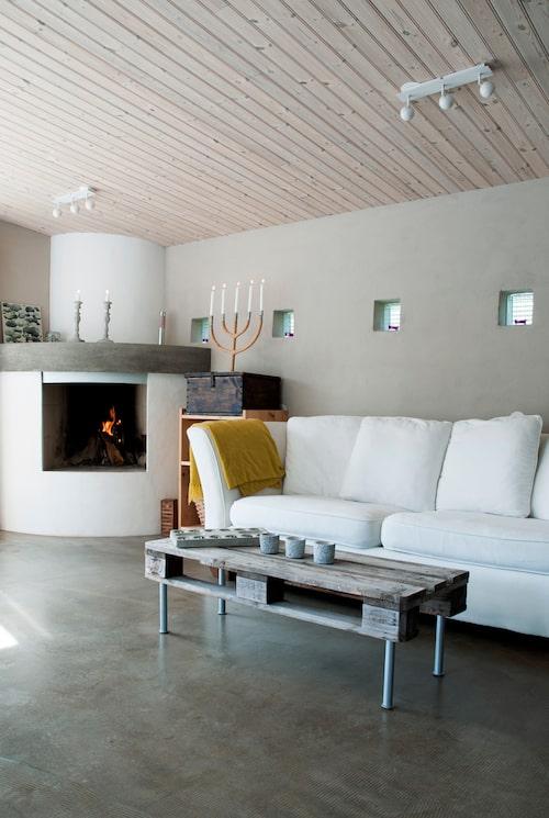 I uterummet värmer den egendesignade och murade spisen gott. Soffbordet har Jens gjort av en gammal SJ-pall.