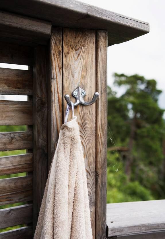 På rad. Flera krokar av klassiskt äldre snitt har skruvats i träskyddet med plats för handdukar, kläder och badkappor.