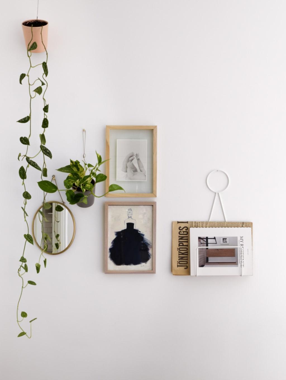 """Hängande. På väggen sitter en tidningshållare från Designtorget och en spegel från Lagerhaus. """"Jag älskar att hänga växter på väggarna, de mjukar upp intrycket"""", säger Emma."""