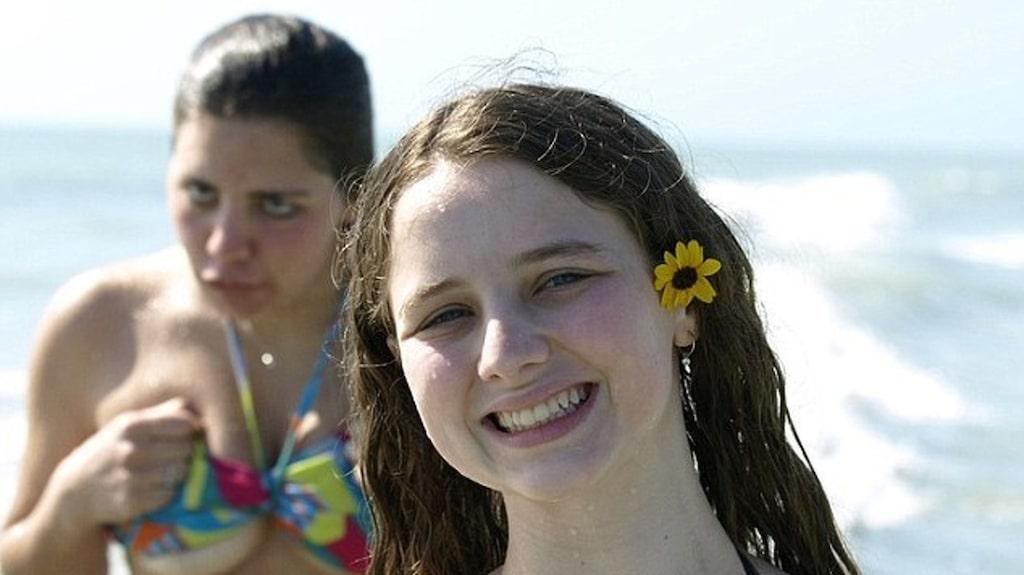 Tjejen i fronten ler men hon i bakgrunden tycks ha seriösa problem med sin bikinitopp.