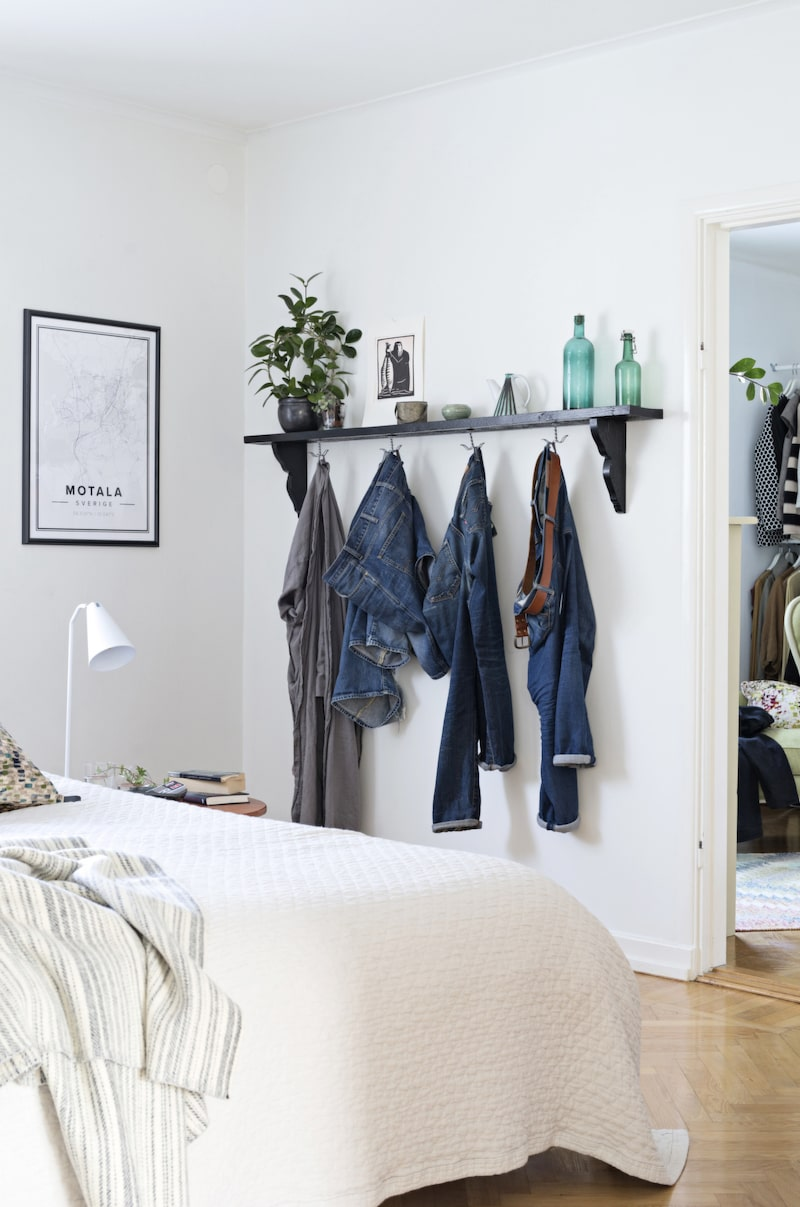 Under hyllplanet i sovrummet hänger jeans på rad, både dekorativt och praktiskt.